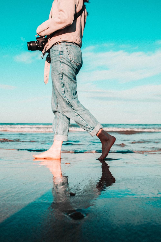 woman holding camera while walking on seashore