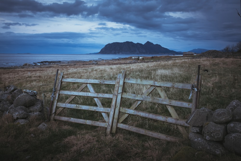brown and gray wooden fence on brown field