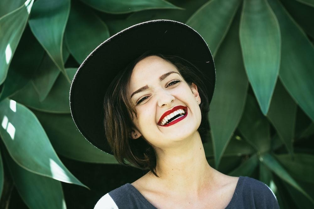 植物の横に立っている笑顔の女性