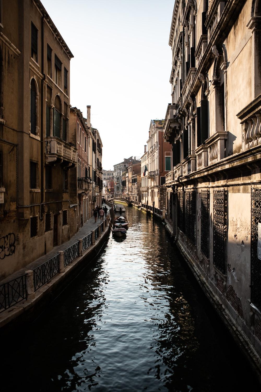 brown boat on body of water between brown houses