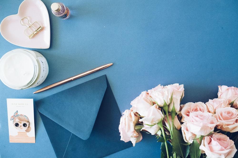 blue envelope beside roses