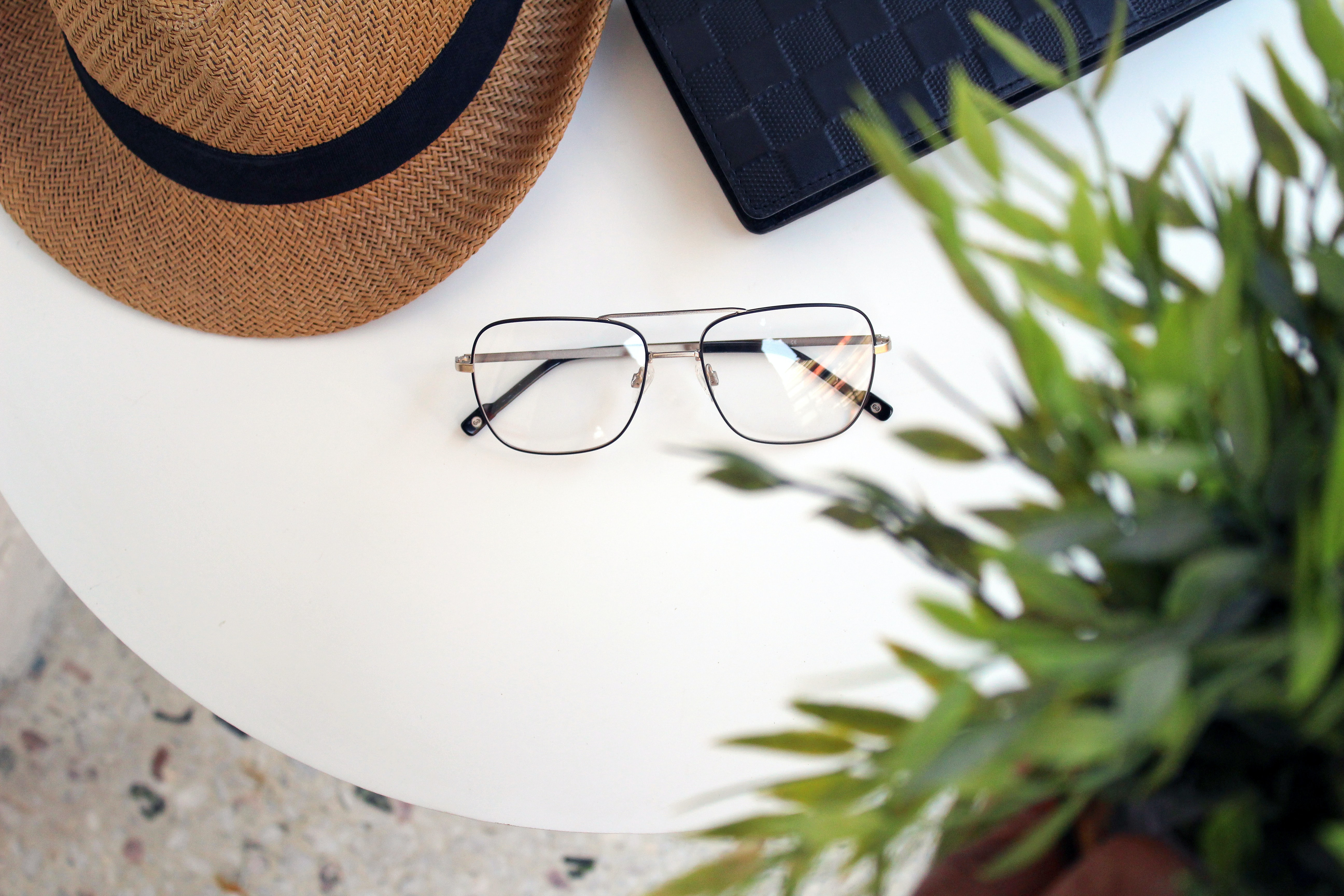 flat lay photography of sunglasses beside sun hat on table
