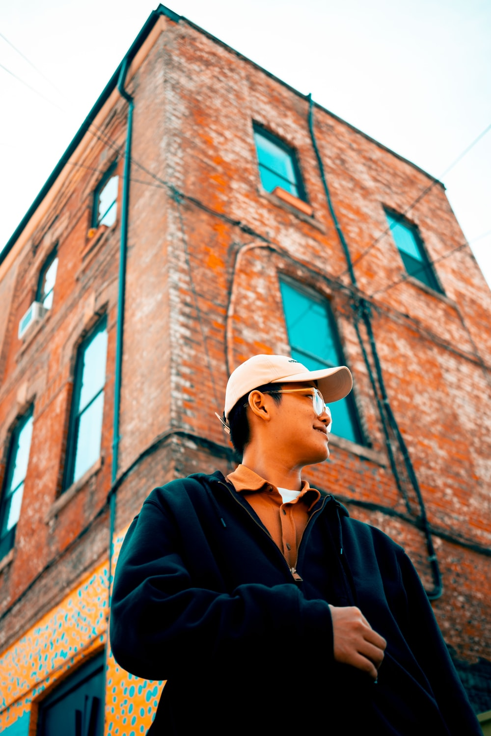 man standing beside red concrete building during daytime