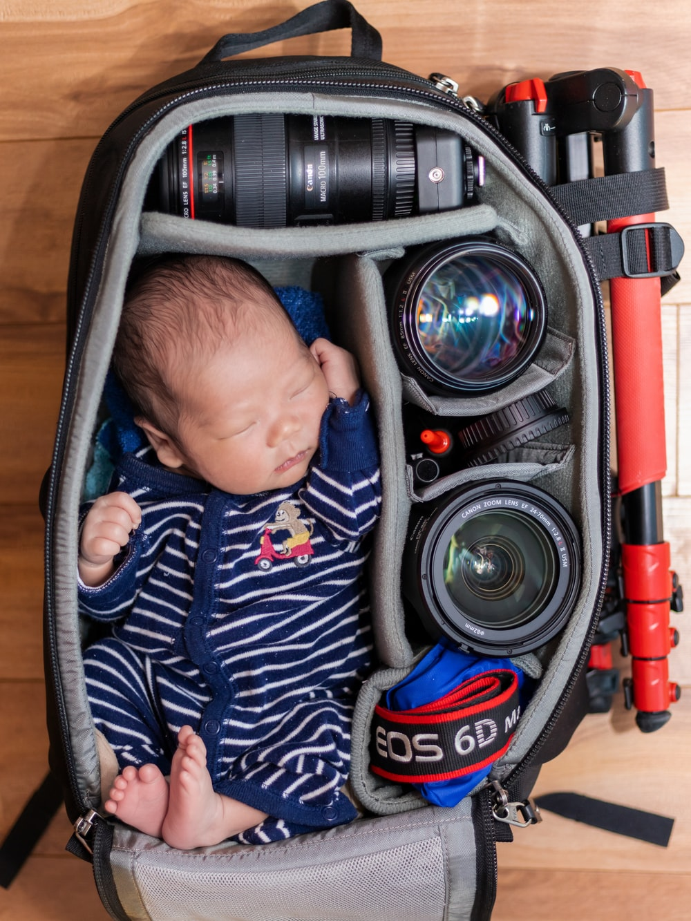 sleeping baby in a camera bag with camera lenses