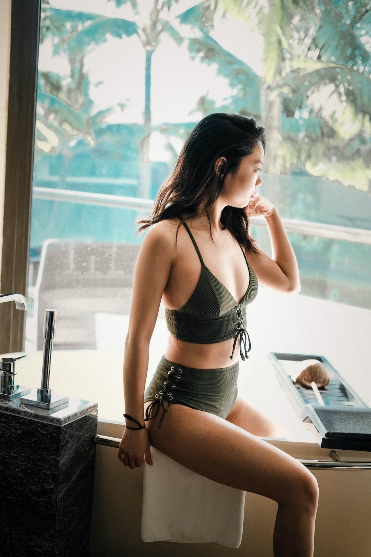 woman wearing black bikini set while sitting on grey metal bar