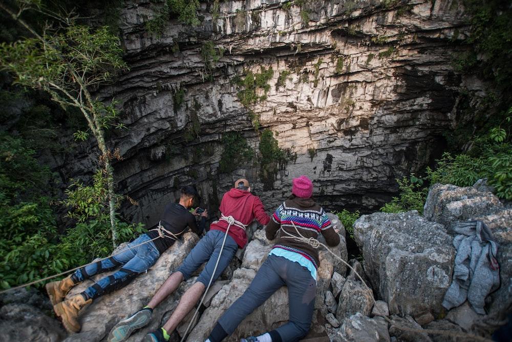 three people lying on boulders