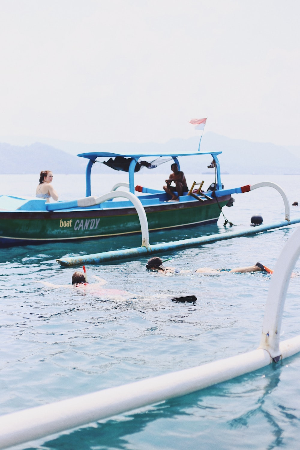 man and woman sitting in motorboat near two person swimming during daytime