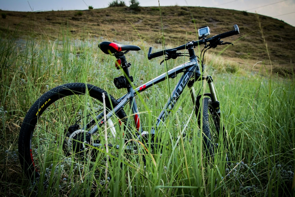 grey and black bicycle parked near grass on hill
