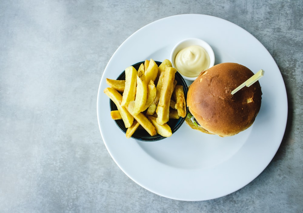 bowl of fries beside burger served on white plate