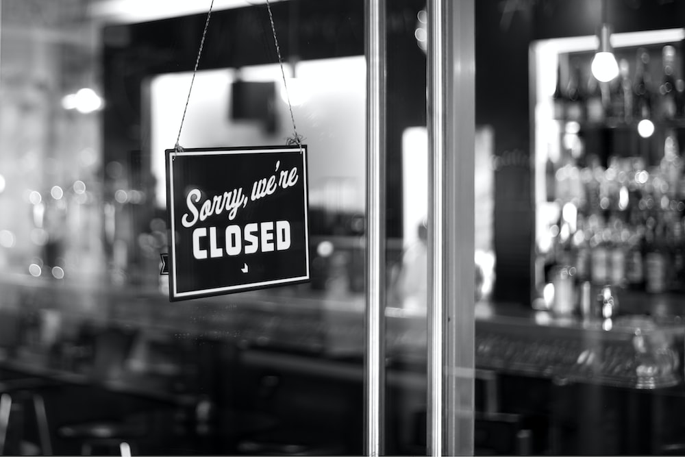 sorry, we're closed signboard hanging on glass door