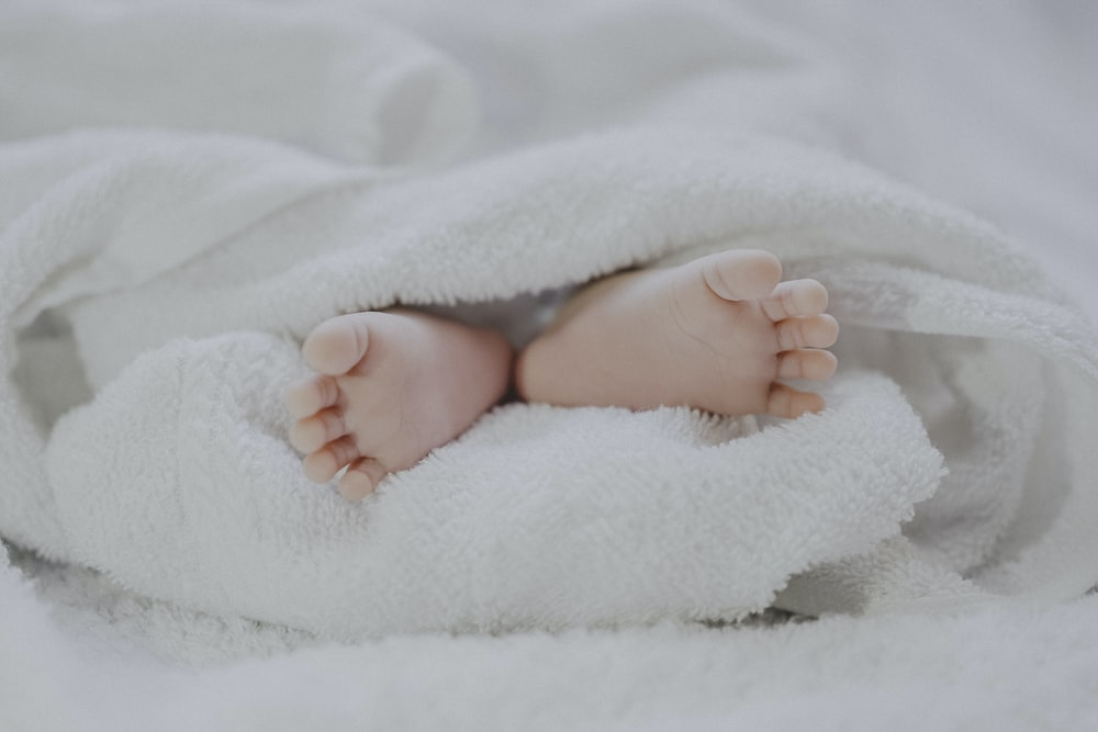 barefooted baby covering white blanket