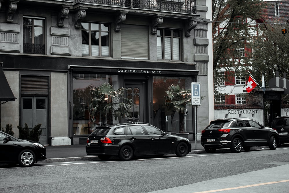cars parked by building during daytime