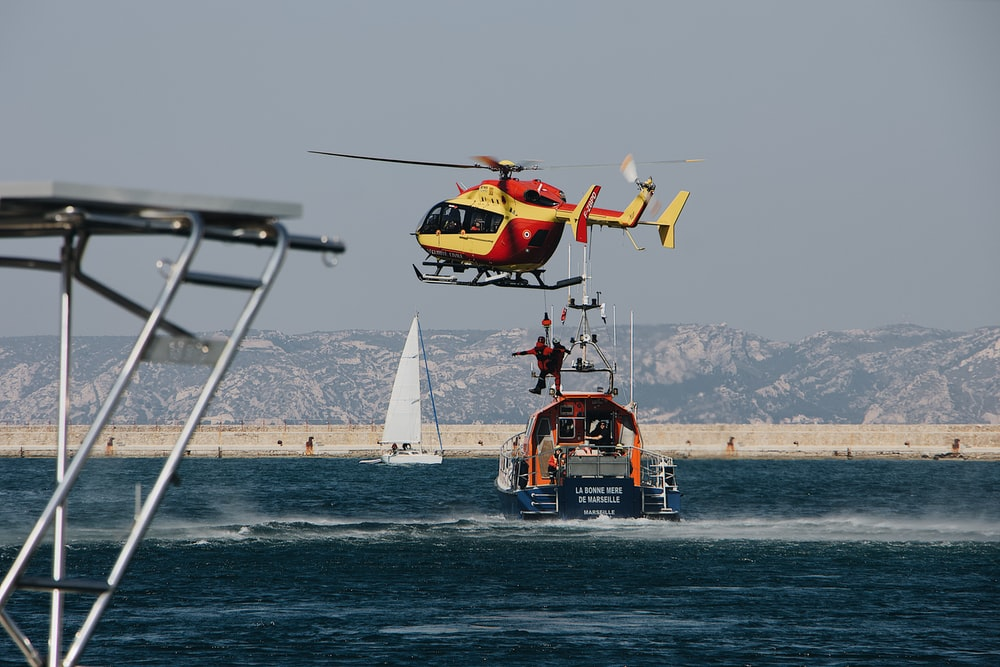 red and yellow helicopter flying above sea during daytime