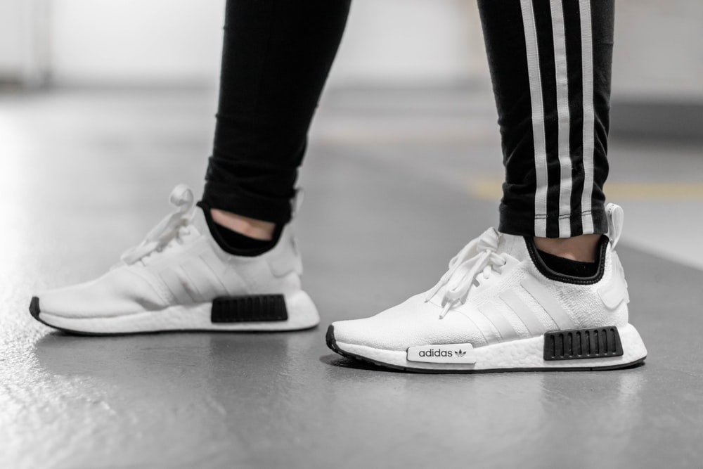 person wearing white Adidas NMD shoes