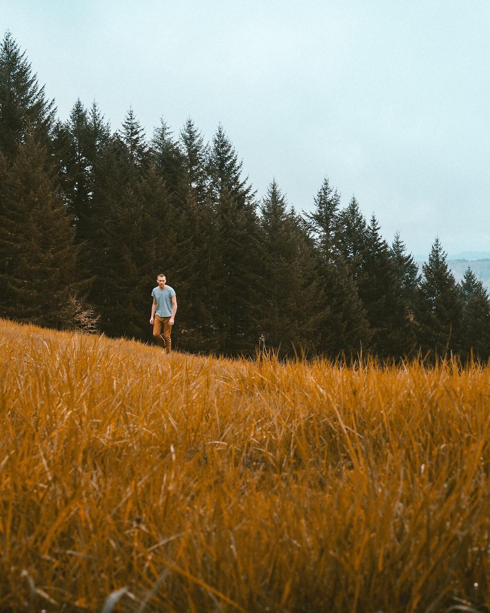 man standing on brown grass field