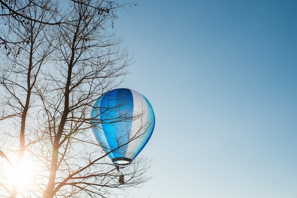 blue and white hot air balloon flying in the sky