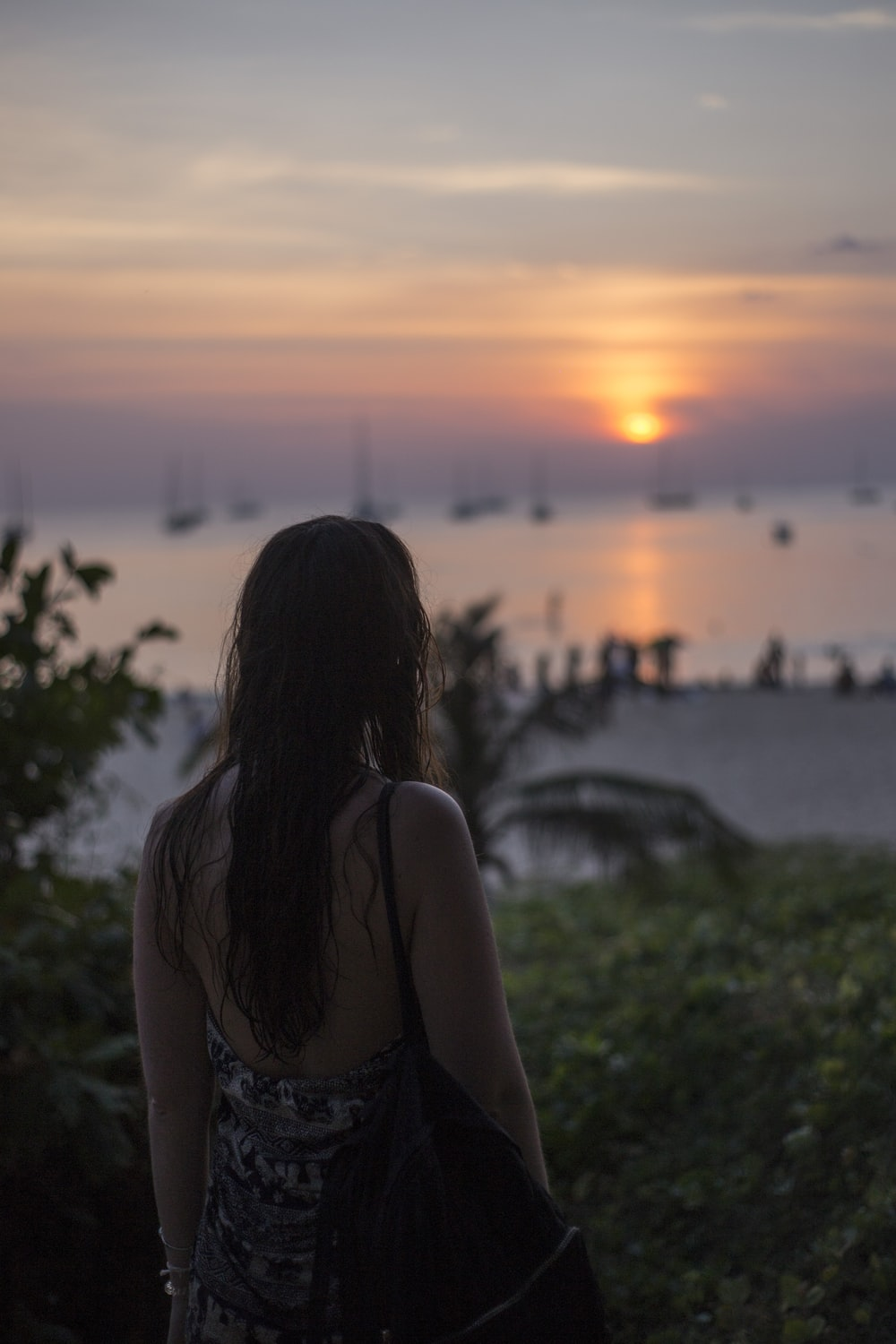 woman in backless top looking into sunset