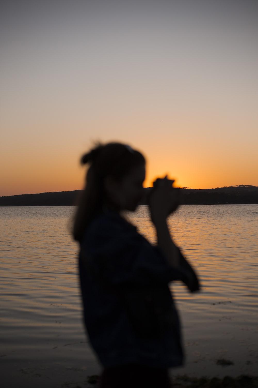 silhouette of woman near body of water