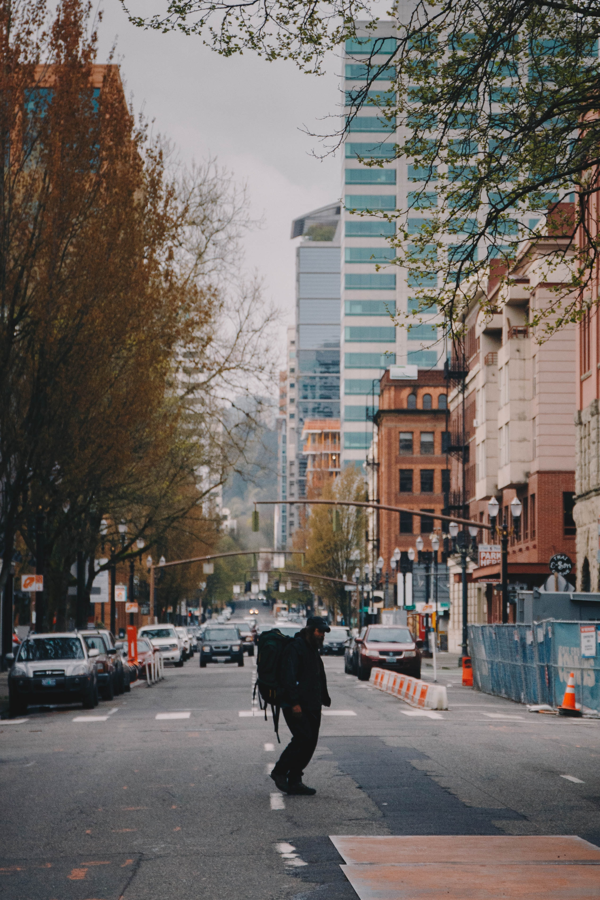 man carrying backpack walking on road