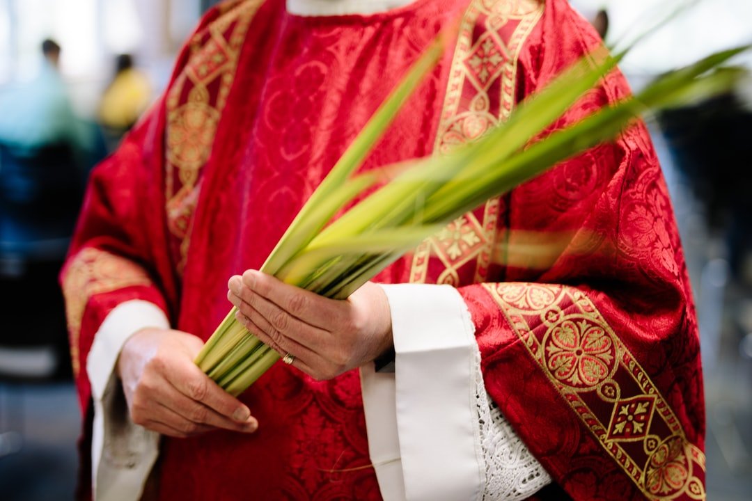 Catholic Priest holding palm fronds on Palm Sunday.