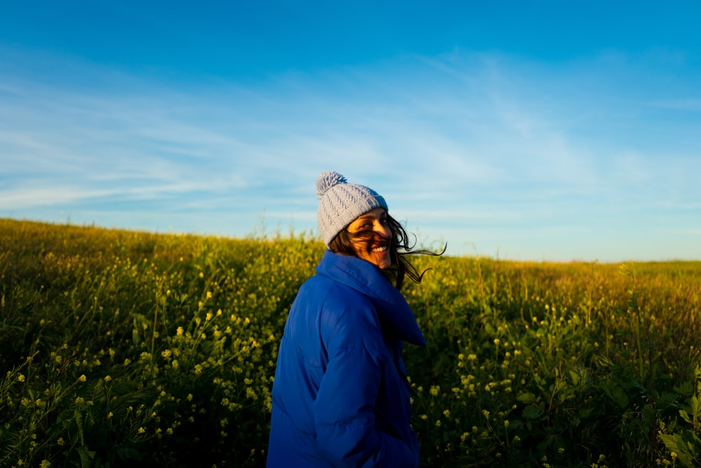 woman wearing blue jacket and ball knit cap standing on field