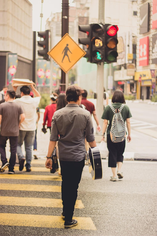 man wearing gray dress shirt standing near traffic light