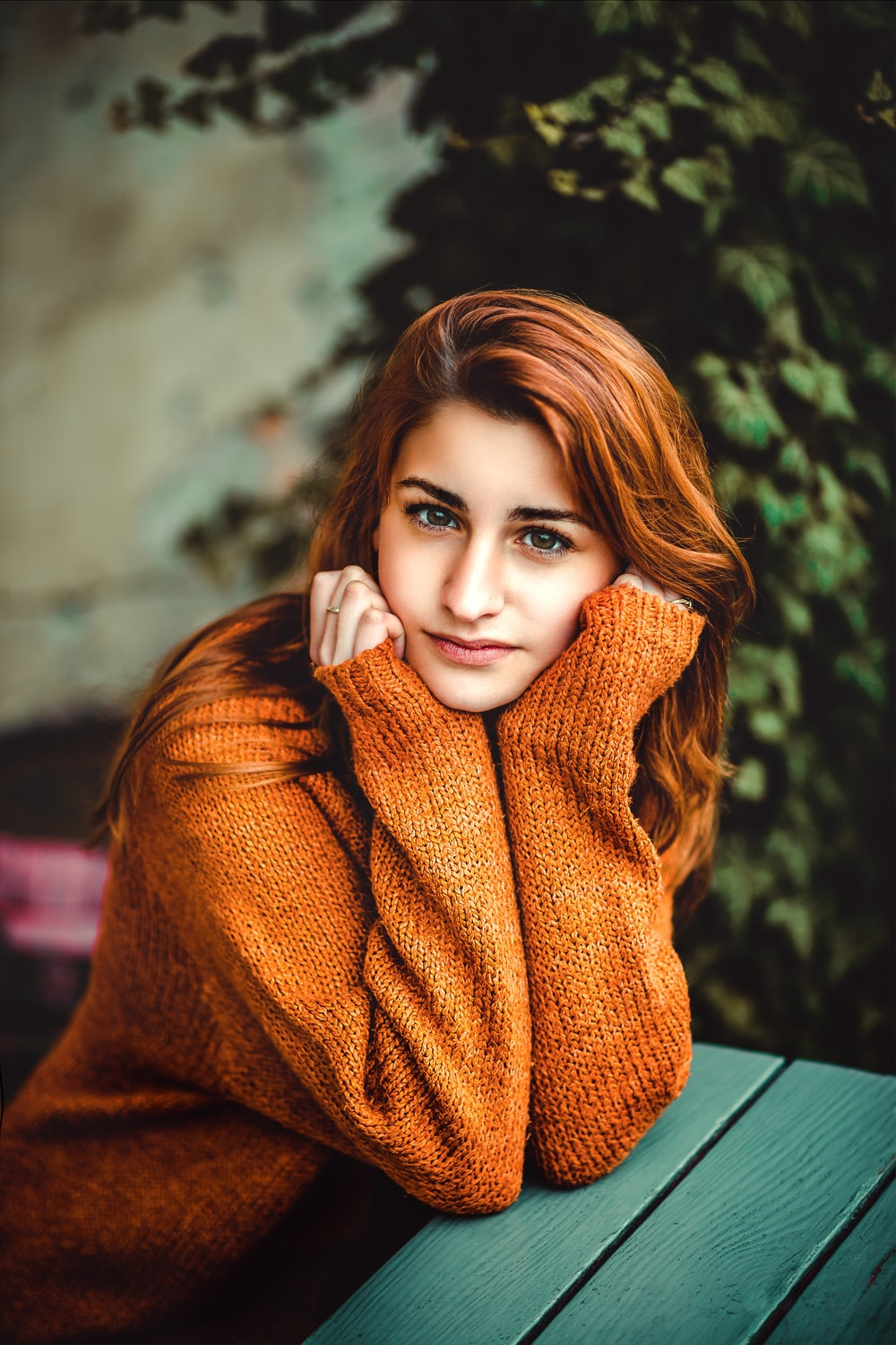 woman in brown knit sweater on green table