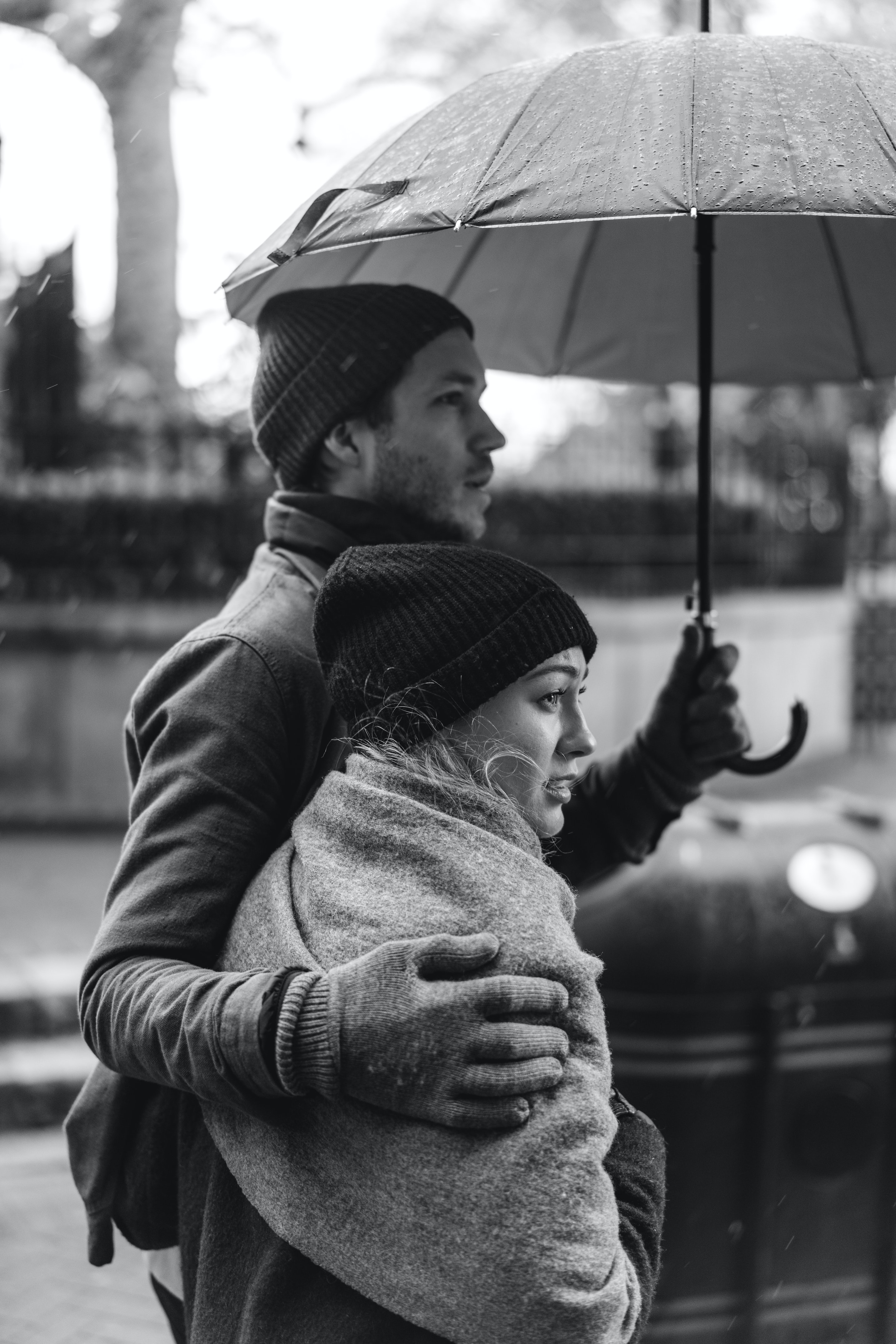 grayscale photography of couple under umbrella