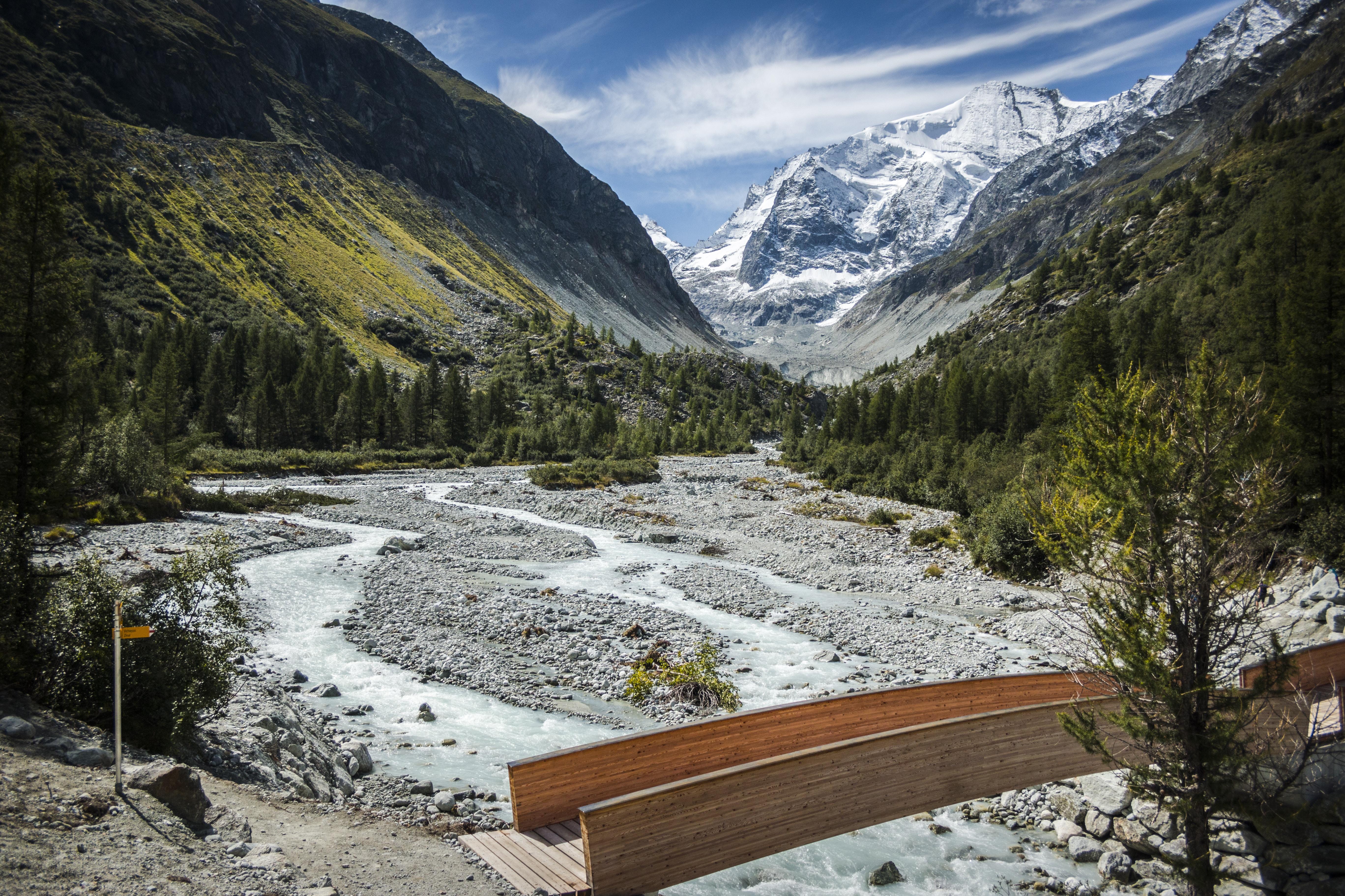 gray rocks and bod of water below brown wooden bridge