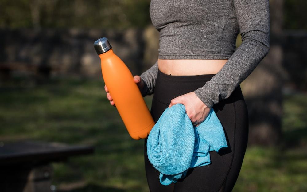 woman in grey long-sleeved shirt holding orange bottle