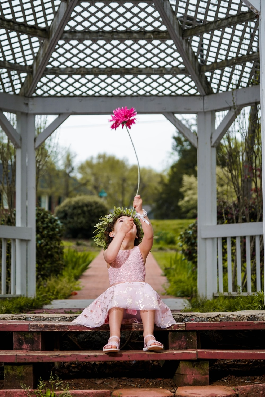 girl holding pink cluster flower under chupa