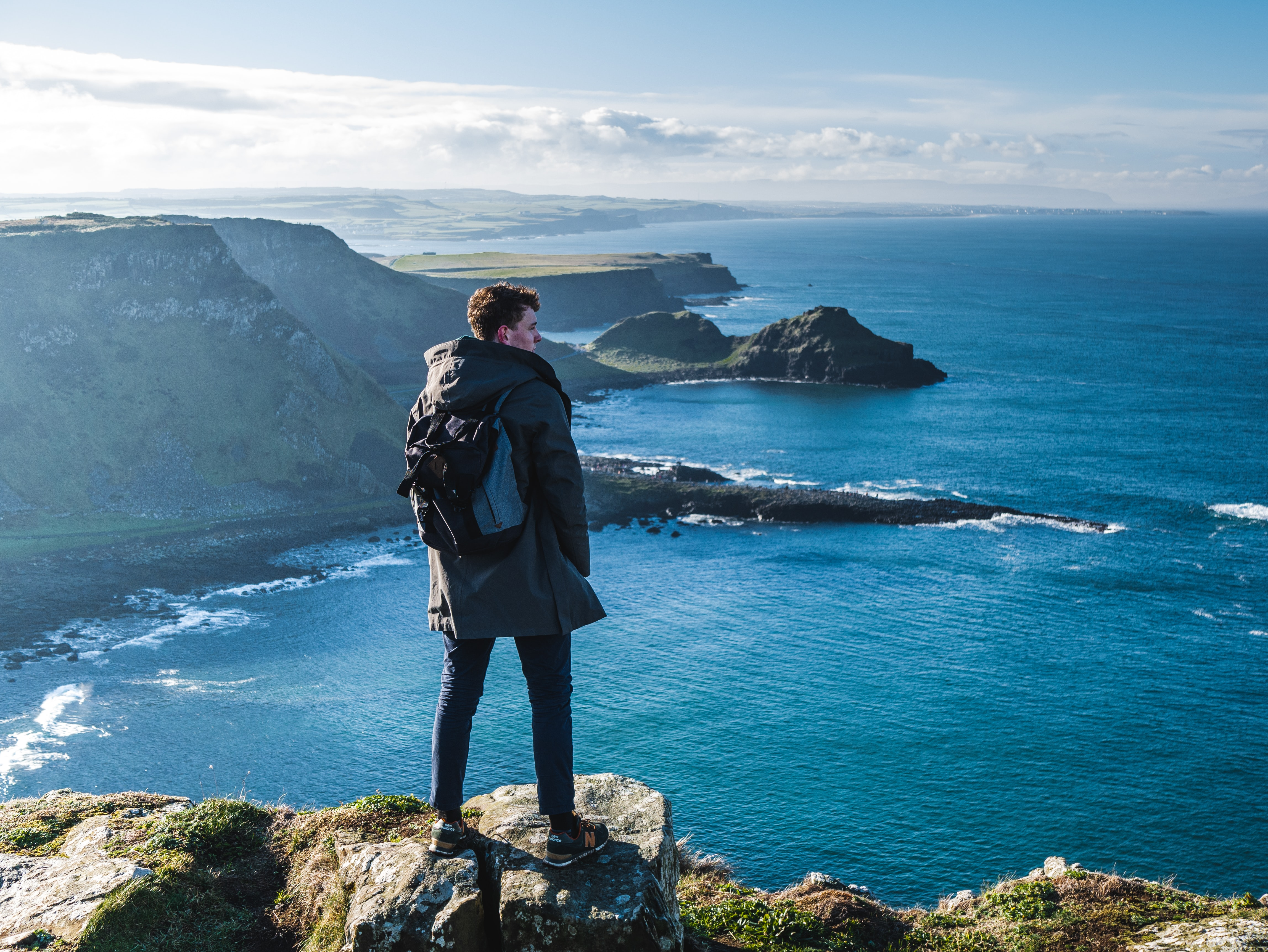 man standing on cliff looking on clear blue sea during daytime