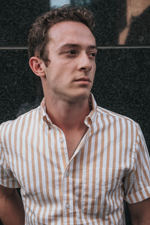 man wearing brown striped shirt