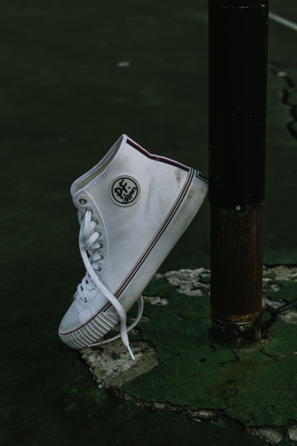 unpaired white PF high-top sneaker leaning on black post