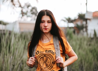 woman wearing orange crew-neck T-shirt with backpack