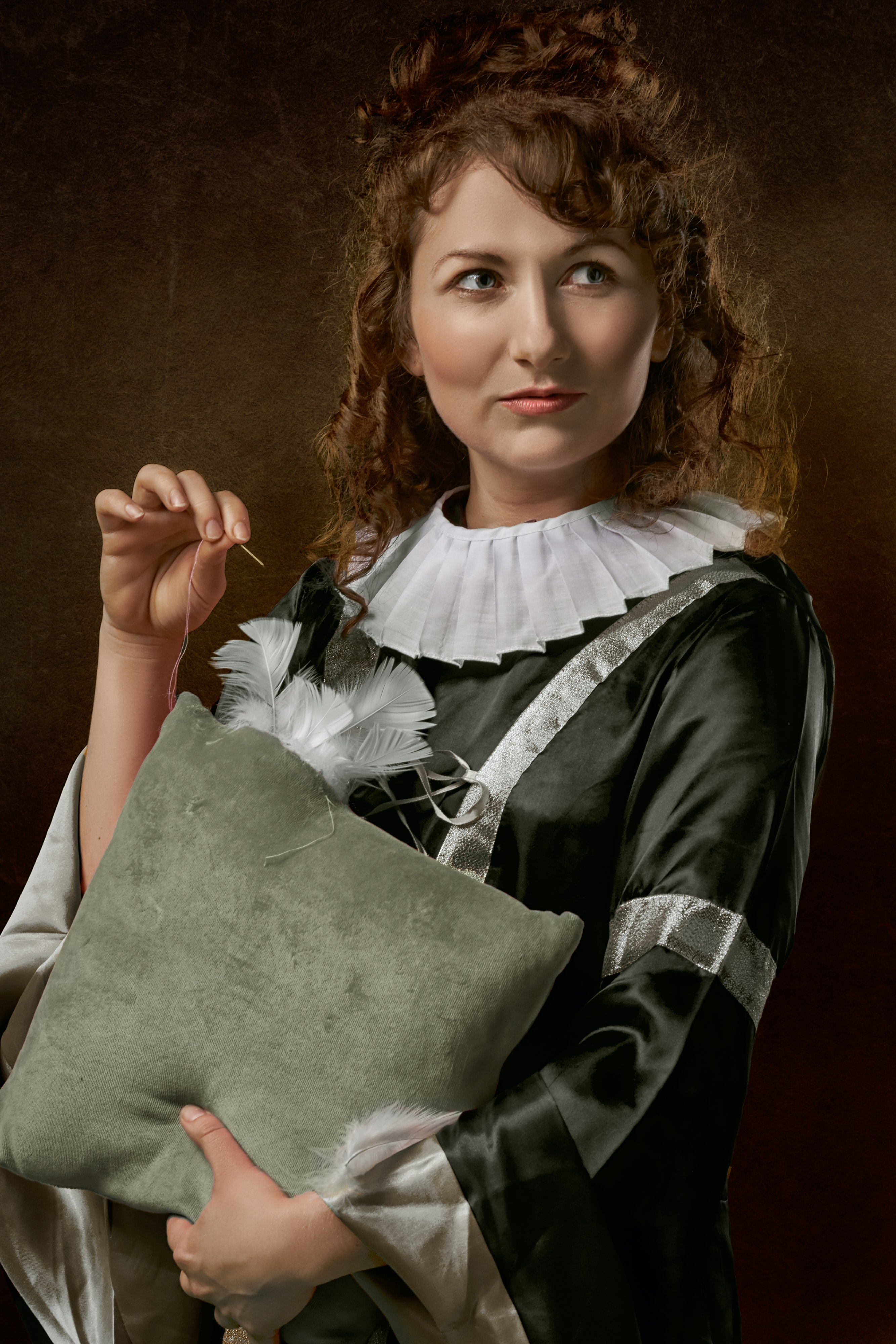 woman looking her left side holding throw pillow and about to sew