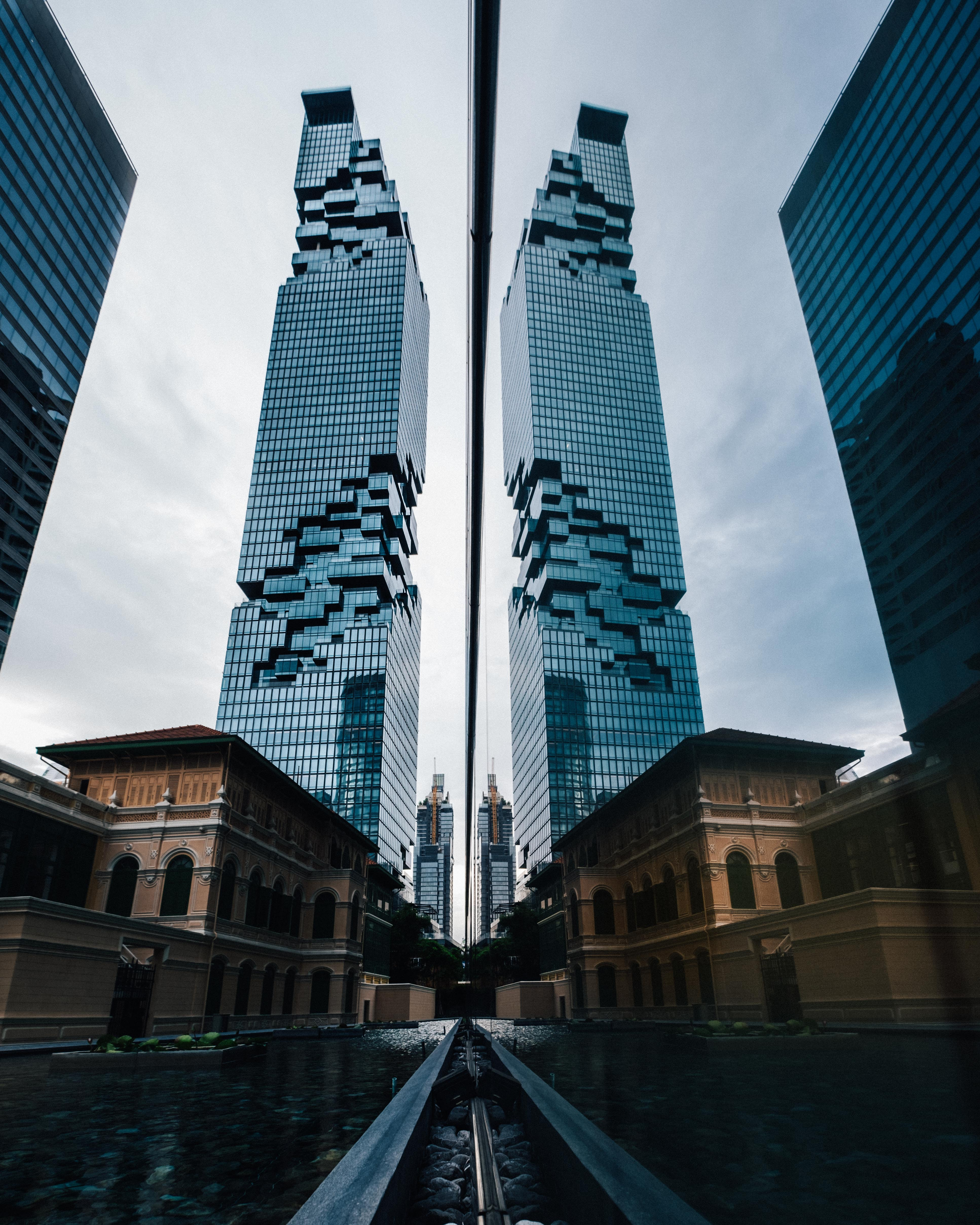 low angle photography of curtain wall building reflecting on mirror