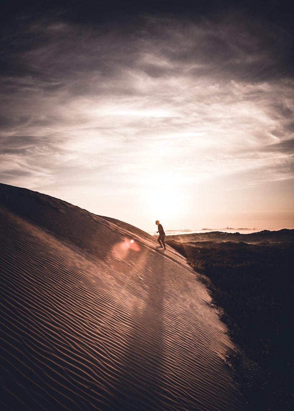 man walking up on sand