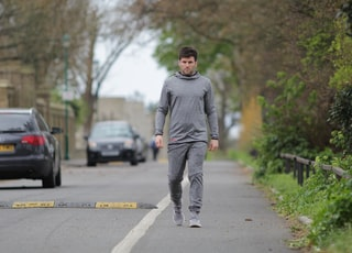 man walking on road near vehicles