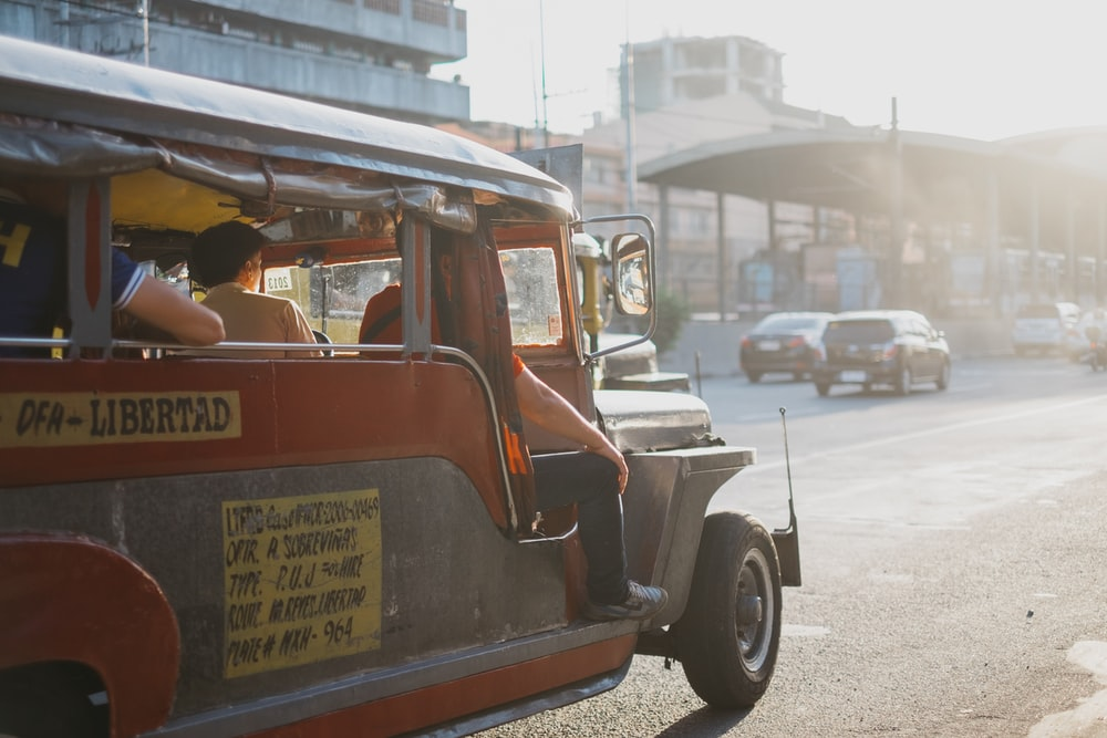 people riding on jeepney during daytime