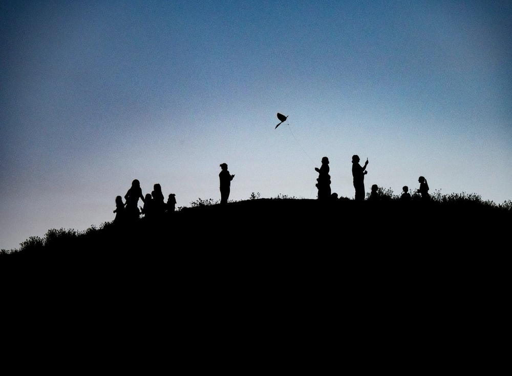 silhouette photography of people on top of a land formation