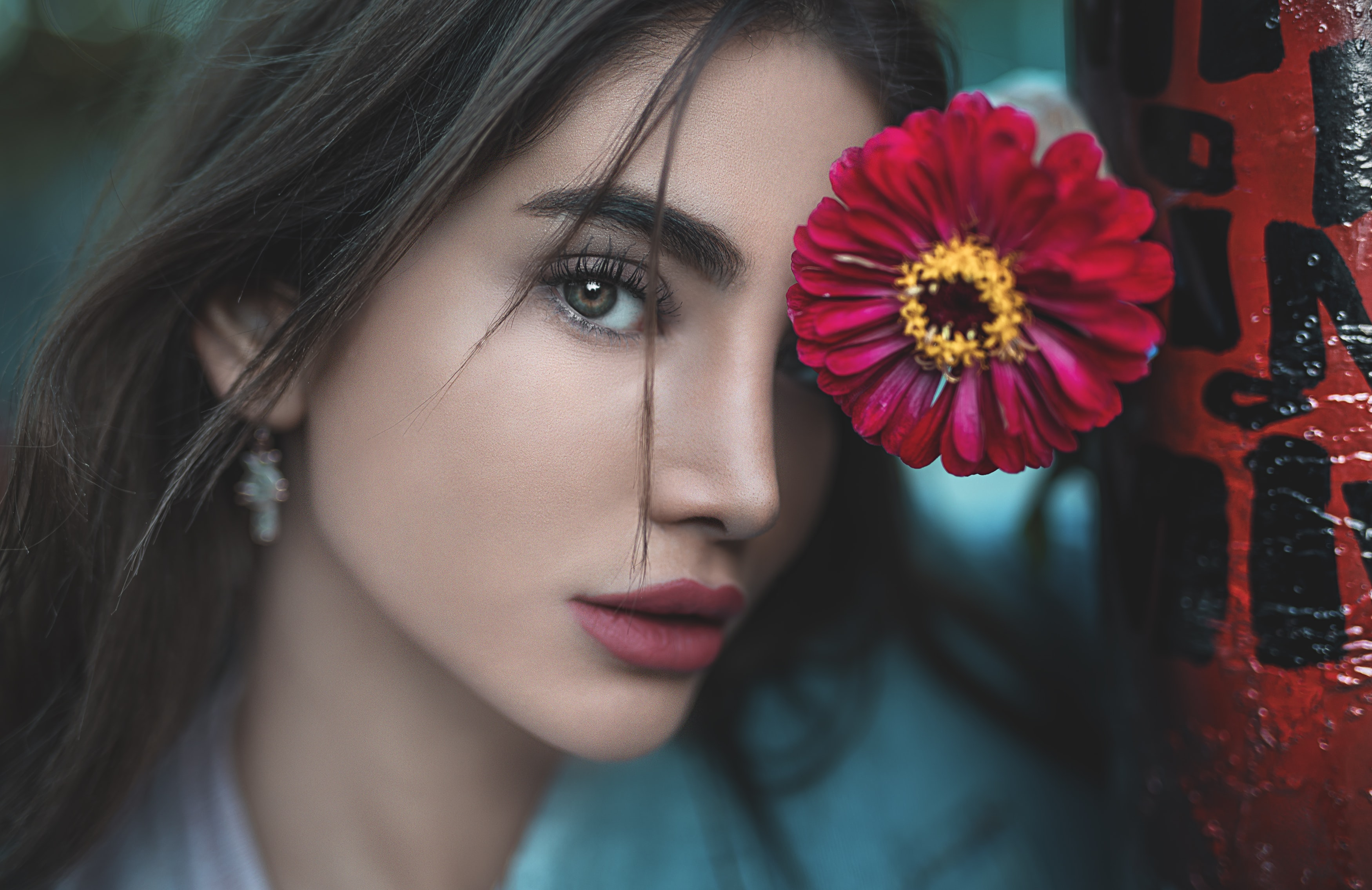 woman leaning on red-petaled flower