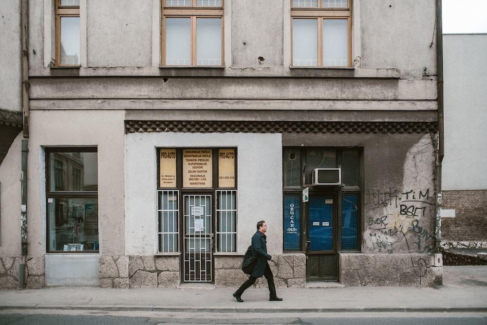 man wearing black coat walking on street