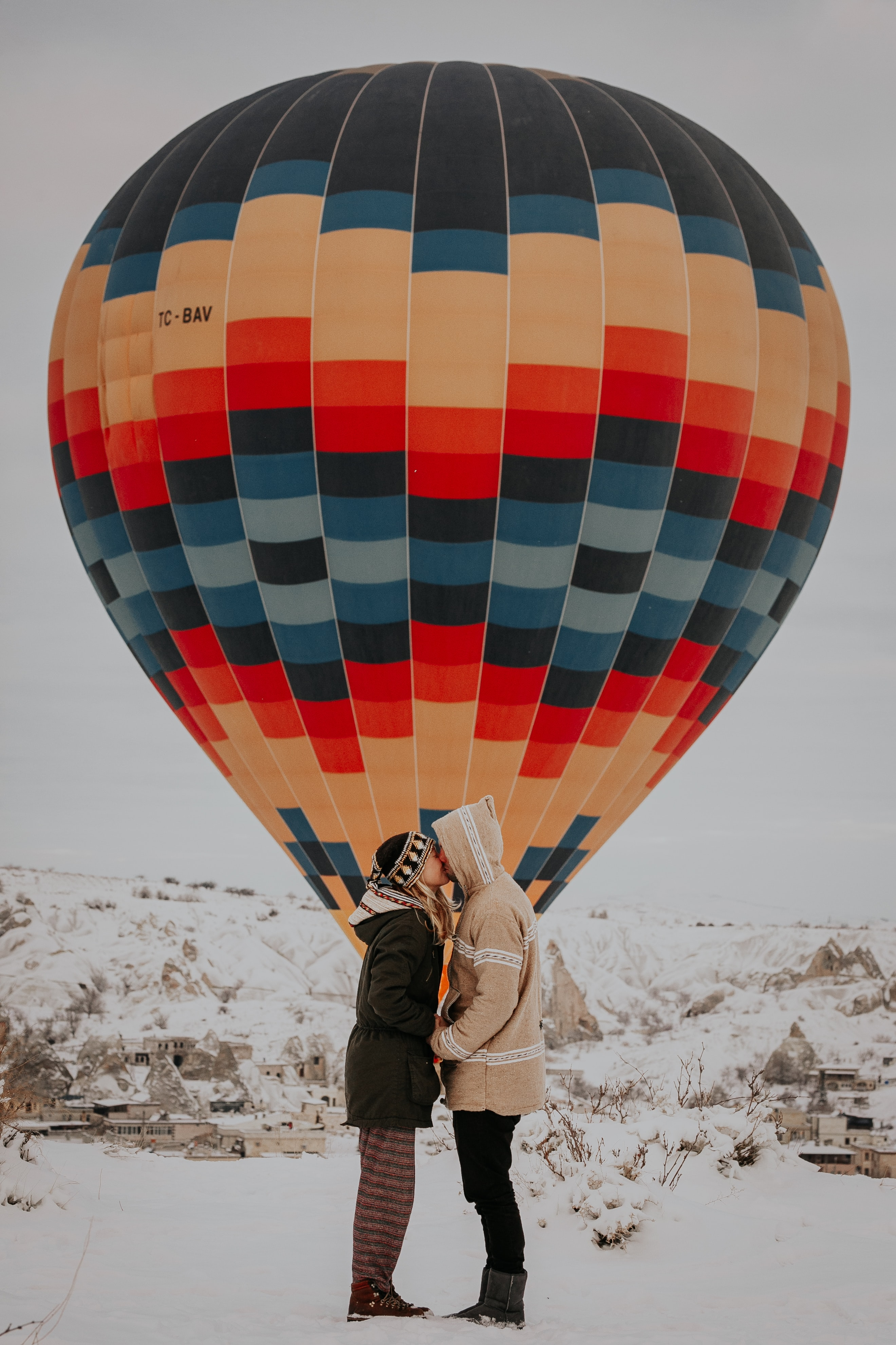coupe kissing standing near hot air balloon
