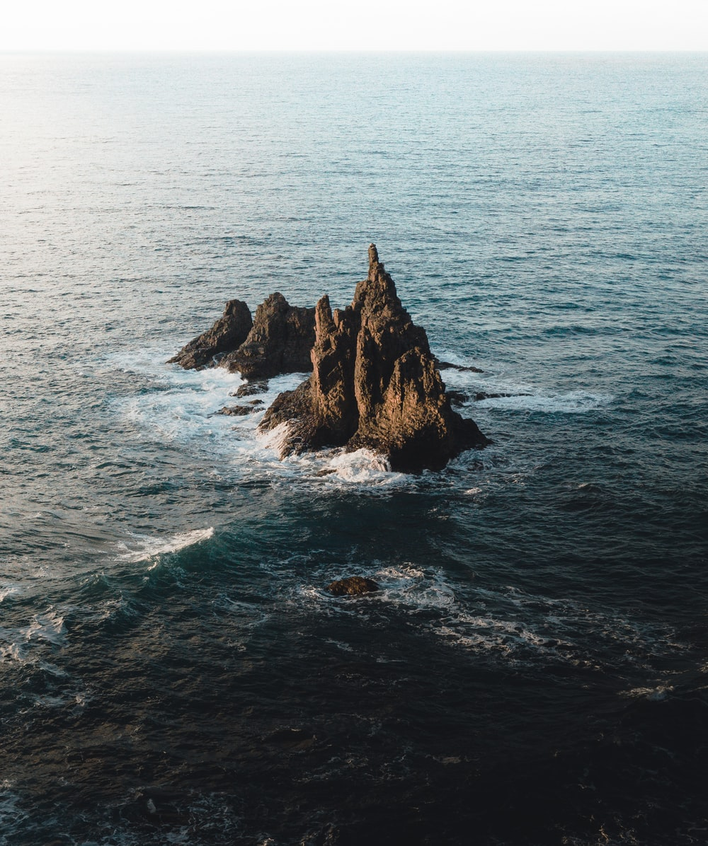 brown rock formation in body of water