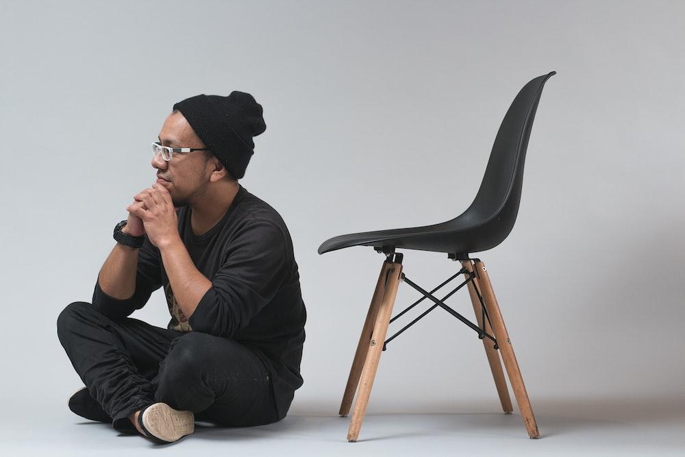 man sitting near black chair