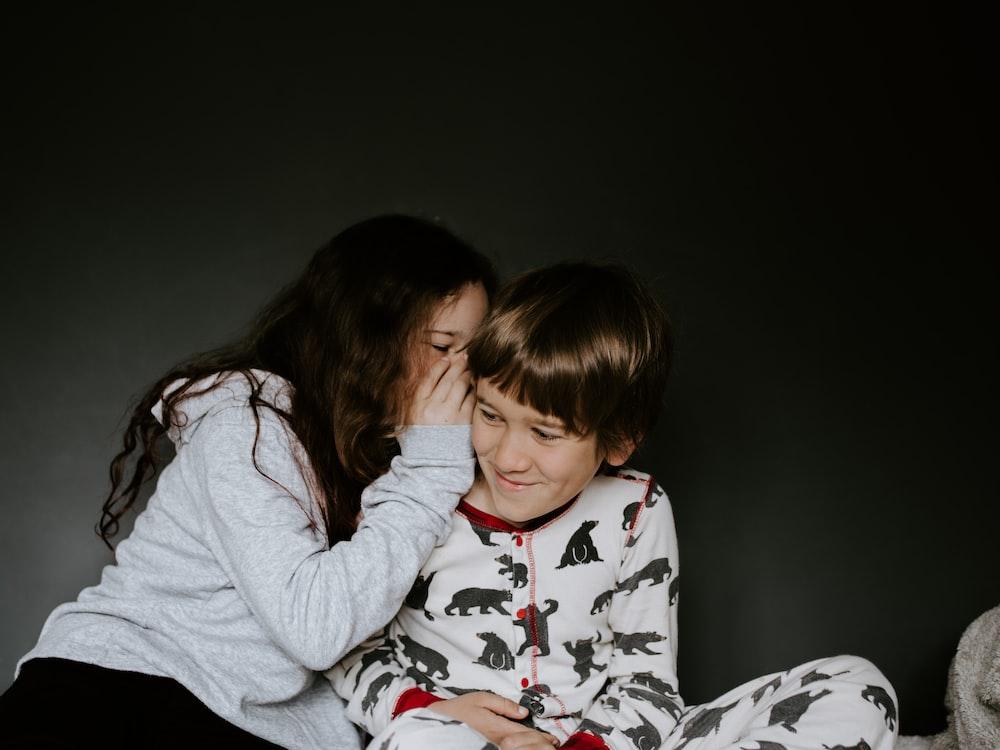 girl in gray jacket whispering on boy's right ear