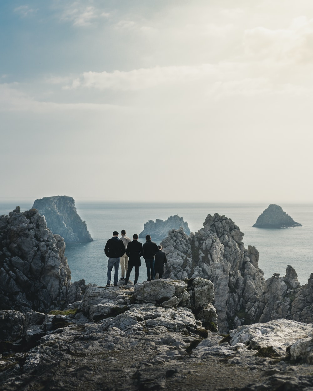 five person standing on rocky hill viewing calm sea