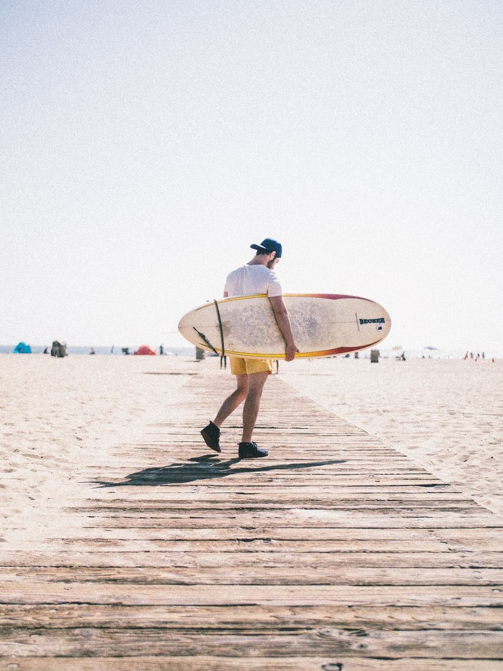 man carrying surfboard while walking on wooden pathway