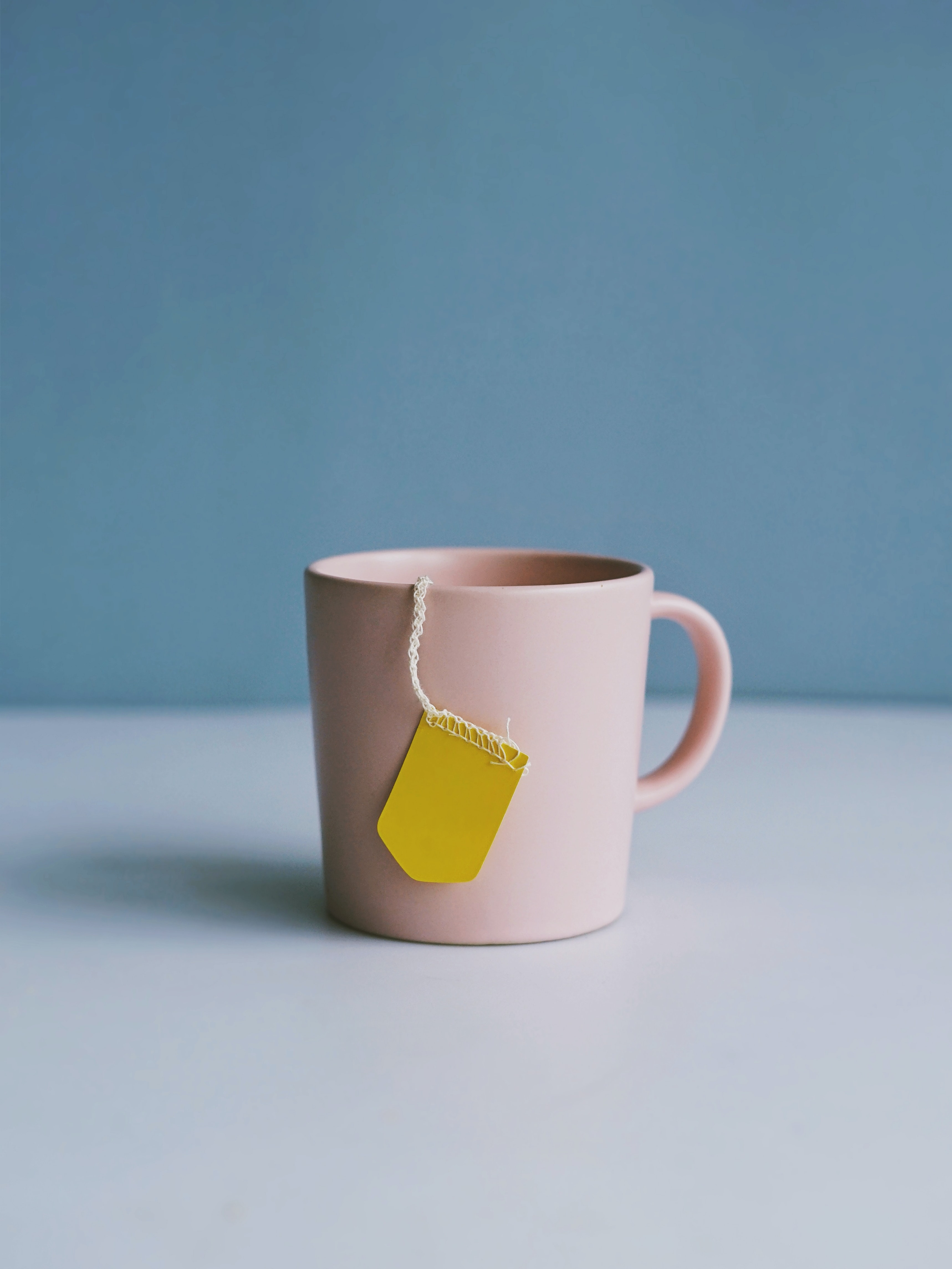 white ceramic mug on white surface